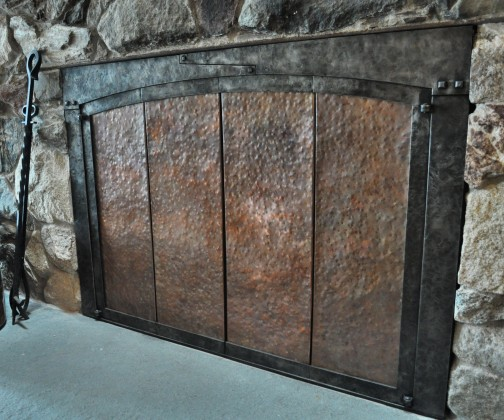 hammered copper and steel bi-fold fireplace doors